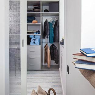 Imagen de armario vestidor unisex, contemporáneo, de tamaño medio, con armarios abiertos, puertas de armario grises, suelo de corcho y suelo gris
