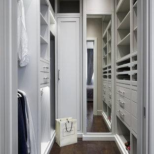 Immagine di una cabina armadio unisex tradizionale con ante con riquadro incassato, ante bianche, parquet scuro e pavimento marrone