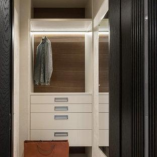 Идея дизайна: маленькая гардеробная комната в современном стиле с плоскими фасадами, бежевыми фасадами, пробковым полом и белым полом для мужчин