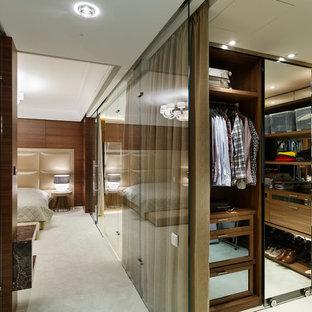 Выдающиеся фото от архитекторов и дизайнеров интерьера: гардеробная комната унисекс в современном стиле с стеклянными фасадами, ковровым покрытием и бежевым полом