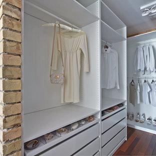Imagen de armario vestidor unisex, actual, con puertas de armario blancas, suelo de madera oscura, suelo marrón y armarios abiertos