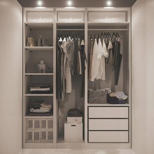 Ejemplo de armario vestidor de mujer, actual, pequeño, con armarios con paneles lisos, puertas de armario blancas, suelo de baldosas de porcelana y suelo blanco