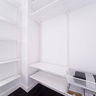 Immagine di una cabina armadio minimal di medie dimensioni con pavimento nero
