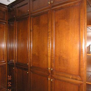 Immagine di un armadio o armadio a muro vittoriano di medie dimensioni con ante con riquadro incassato, ante marroni e pavimento in legno massello medio