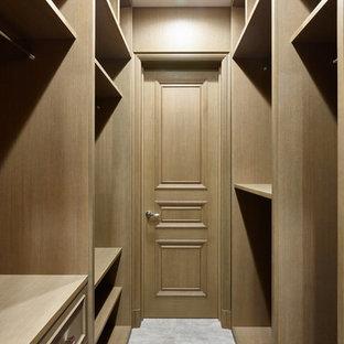 Идея дизайна: гардеробная комната унисекс в стиле современная классика с фасадами с утопленной филенкой, фасадами цвета дерева среднего тона и серым полом