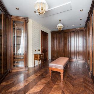 На фото: парадная гардеробная унисекс в классическом стиле с фасадами цвета дерева среднего тона и паркетным полом среднего тона с