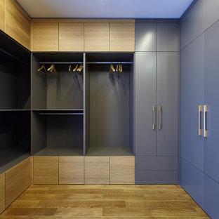 На фото: большая гардеробная комната унисекс в современном стиле с фасадами цвета дерева среднего тона, полом из ламината, бежевым полом и плоскими фасадами