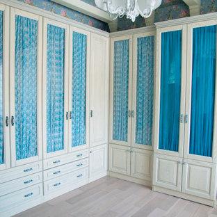 Imagen de armario vestidor unisex, tradicional, grande, con armarios tipo vitrina, puertas de armario blancas y suelo de madera clara