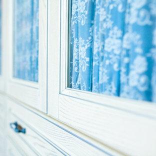 モスクワの広い男女兼用トラディショナルスタイルのおしゃれなウォークインクローゼット (ガラス扉のキャビネット、白いキャビネット、淡色無垢フローリング、表し梁) の写真