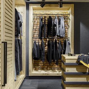 Idée de décoration pour un dressing room urbain pour un homme avec un placard sans porte et un sol gris.