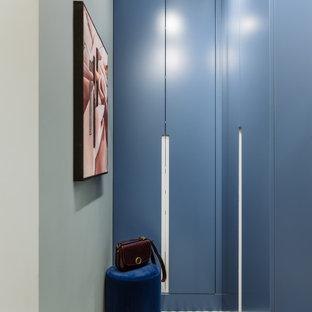 На фото: гардеробная унисекс в современном стиле с плоскими фасадами и синими фасадами с
