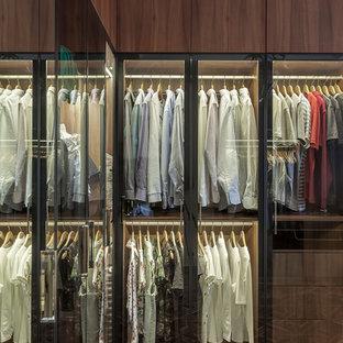 На фото: гардеробная в современном стиле с паркетным полом среднего тона, плоскими фасадами и темными деревянными фасадами для мужчин с