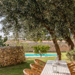 Idee per un grande giardino mediterraneo esposto in pieno sole davanti casa in estate con un muro di contenimento e pavimentazioni in pietra naturale