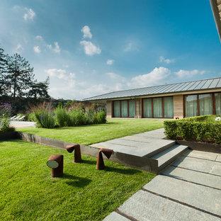 Inspiration pour un grand jardin à la française latéral design avec des pavés en pierre naturelle.