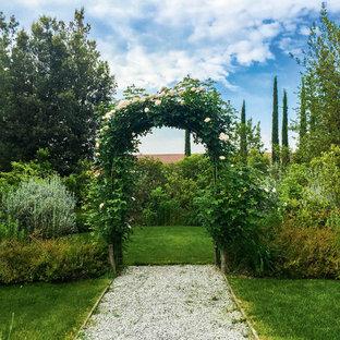 Idee per un grande giardino formale mediterraneo esposto a mezz'ombra in primavera con ghiaia