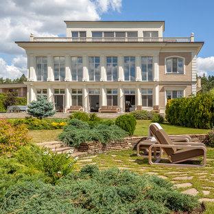 На фото: большой солнечный, летний участок и сад на переднем дворе в современном стиле с подпорной стенкой и хорошей освещенностью с