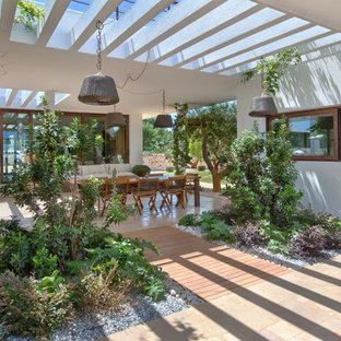 Новые идеи обустройства дома: участок и сад среднего размера на внутреннем дворе в средиземноморском стиле с подъездной дорогой, полуденной тенью и настилом