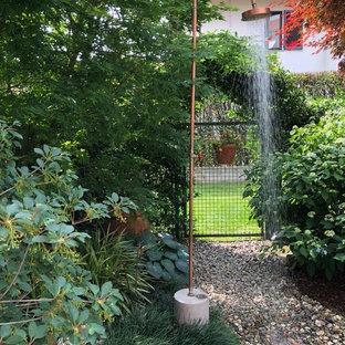 Immagine di un piccolo giardino industriale in ombra dietro casa in primavera con un ingresso o sentiero e ghiaia