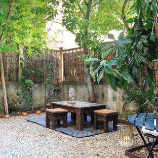 Idee per un giardino xeriscape etnico esposto a mezz'ombra di medie dimensioni e dietro casa con un muro di contenimento e ghiaia