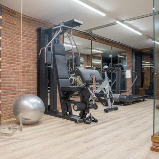 Multifunktionaler, Mittelgroßer Industrial Fitnessraum mit oranger Wandfarbe und hellem Holzboden in Barcelona
