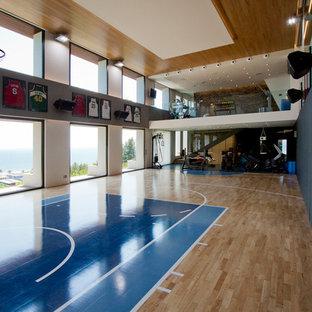 Esempio di un grande campo sportivo coperto moderno con pareti multicolore e pavimento in legno massello medio