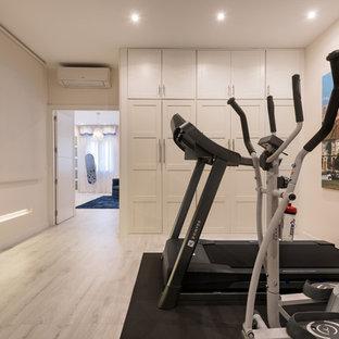 Exemple d'une grand salle de sport tendance multi-usage avec un mur blanc et un sol en bois clair.
