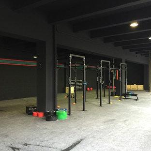 Geräumiger, Multifunktionaler Industrial Fitnessraum mit schwarzer Wandfarbe und Betonboden in Sonstige
