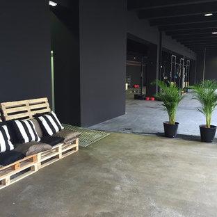 Idee per un'ampia palestra multiuso industriale con pareti nere e pavimento in cemento