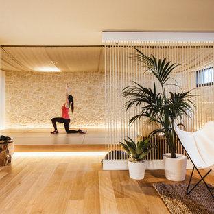 Foto de estudio de yoga mediterráneo con suelo de madera clara, paredes beige y suelo beige