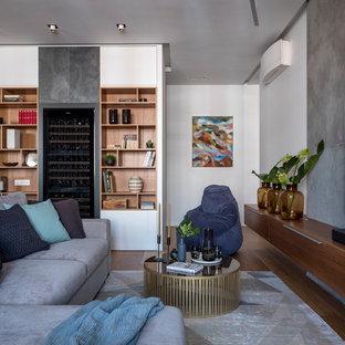На фото: парадная гостиная комната в современном стиле с белыми стенами, паркетным полом среднего тона, телевизором на стене и коричневым полом