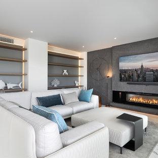 На фото: открытая гостиная комната среднего размера в современном стиле с горизонтальным камином, фасадом камина из металла, телевизором на стене, белым полом и серыми стенами с