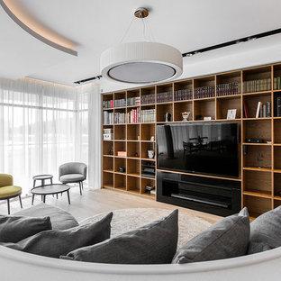 Неиссякаемый источник вдохновения для домашнего уюта: открытая гостиная комната в современном стиле с белыми стенами, светлым паркетным полом и телевизором на стене