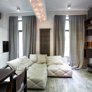 Пример оригинального дизайна интерьера: парадная, открытая гостиная комната в современном стиле с белыми стенами и телевизором на стене