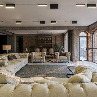 Imagen de salón abierto, industrial, con paredes marrones, suelo de madera en tonos medios, televisor colgado en la pared y suelo beige