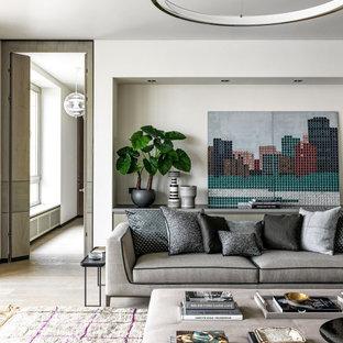 На фото: изолированная гостиная комната среднего размера в современном стиле с белыми стенами, светлым паркетным полом и бежевым полом с