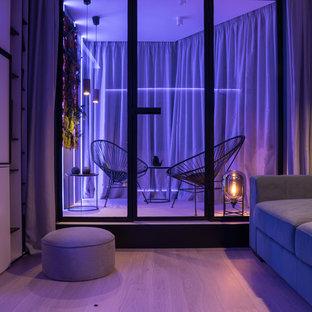 Esempio di un piccolo soggiorno minimal con pareti grigie, parquet chiaro, pavimento beige e TV a parete