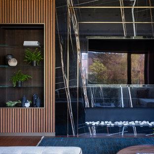 Идея дизайна: гостиная комната в современном стиле с черными стенами, телевизором на стене и коричневым полом