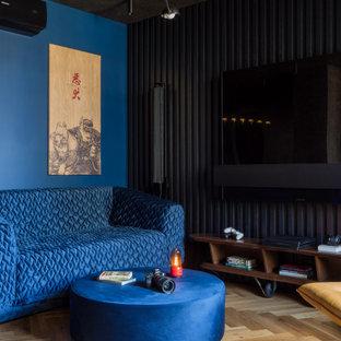 Пример оригинального дизайна: открытая гостиная комната среднего размера в современном стиле с музыкальной комнатой, синими стенами, паркетным полом среднего тона и телевизором на стене без камина