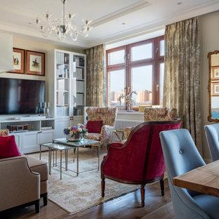 Modelo de salón abierto, tradicional, con paredes beige, suelo de madera oscura, televisor colgado en la pared y suelo marrón