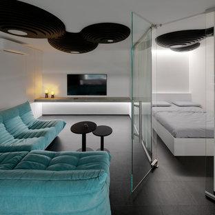 他の地域の中サイズのコンテンポラリースタイルのおしゃれなリビング (白い壁、クッションフロア、壁掛け型テレビ、黒い床) の写真