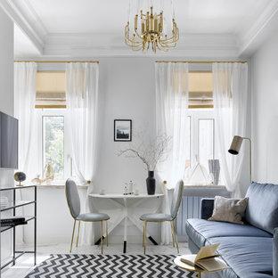 Стильный дизайн: маленькая изолированная гостиная комната в современном стиле с белыми стенами, полом из керамогранита, телевизором на стене и белым полом - последний тренд