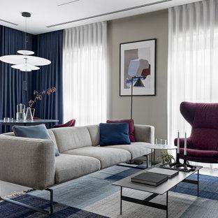 Пример оригинального дизайна: большая открытая гостиная комната в современном стиле с библиотекой, бежевыми стенами, полом из керамогранита, телевизором на стене и коричневым полом без камина
