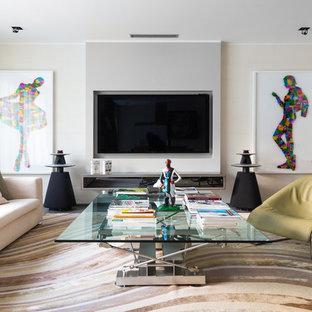 Свежая идея для дизайна: изолированная гостиная комната в современном стиле с бежевыми стенами, телевизором на стене и коричневым полом - отличное фото интерьера