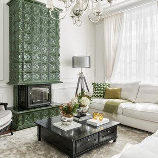 На фото: открытая гостиная комната в классическом стиле с белыми стенами, темным паркетным полом, стандартным камином, фасадом камина из плитки и коричневым полом с
