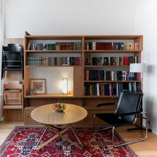 На фото: маленькая гостиная комната в современном стиле с библиотекой, белыми стенами и паркетным полом среднего тона с