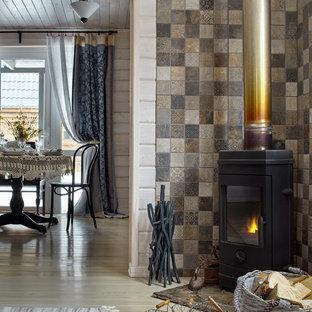 Modelo de salón de estilo de casa de campo con estufa de leña, paredes multicolor y suelo de madera clara