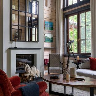 На фото: открытая, парадная гостиная комната среднего размера в стиле кантри с бежевыми стенами, стандартным камином, фасадом камина из штукатурки, паркетным полом среднего тона и коричневым полом с