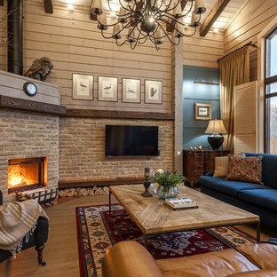 Свежая идея для дизайна: открытая гостиная комната среднего размера в стиле кантри с бежевыми стенами, угловым камином, телевизором на стене, паркетным полом среднего тона, фасадом камина из камня, коричневым полом, балками на потолке и панелями на части стены - отличное фото интерьера