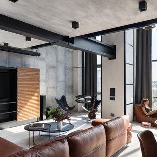 Стильный дизайн: открытая гостиная комната в стиле лофт с серыми стенами, мультимедийным центром и серым полом - последний тренд