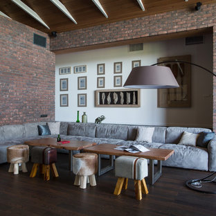 Inspiration for an expansive contemporary formal mezzanine living room in Other with brown walls, laminate floors, a two-sided fireplace, a brick fireplace surround, a freestanding tv and brown floors.